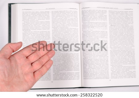 The male palm shows on the big open book with text. - stock photo