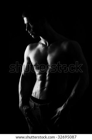The male portrait on black background, low key - stock photo