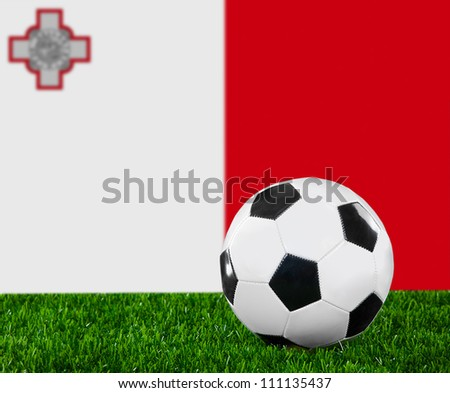 The Maltese flag and soccer ball on the green grass