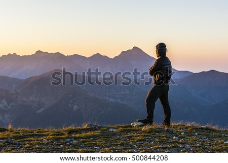 The man admires sunrise in the mountains.