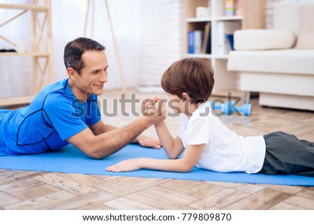 The man and the boy are engaged in arm-wrestling. This is father and son. They are at home.