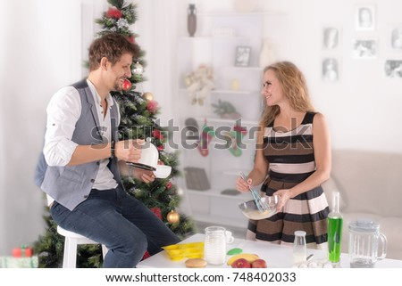 the man and the woman cook food on a holiday table