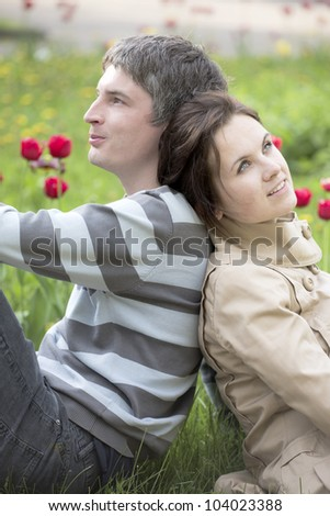 The man and the woman sit against a bed with tulips