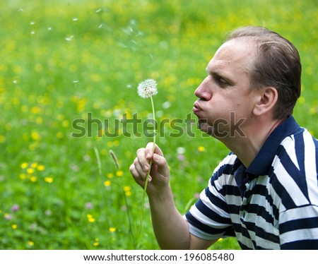 The man blows off fuzzes from a dandelion