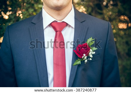 The man blue suite and red tie. The groom on a marriage day. Red tie combined with a red rose in a jacket pocket. Green background.
