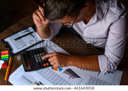 The man (businessman, manager, analyst, student) working with tables, graphs, diagrams, makes calculations at the wooden table in the office in the evening (or at night), after hours