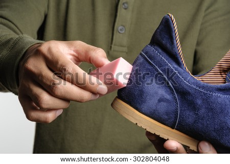 The man cleaning his suede shoe - stock photo