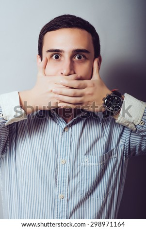 The man closed his mouth with her hands. On a gray background. - stock photo
