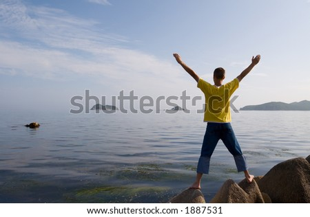 The man costs(stands) on rocks having stretched hands.Evening.Sunset.Coast. - stock photo