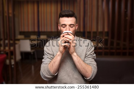 The  man drinking coffee in a restaurant - stock photo
