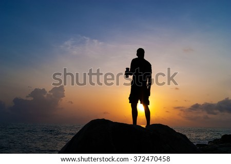 The man drinks from a bottle at dawn