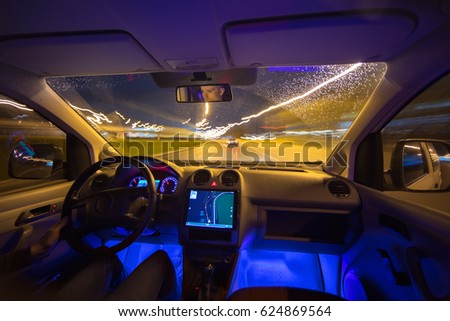 The man drive with a navigation on the night highway. Inside view