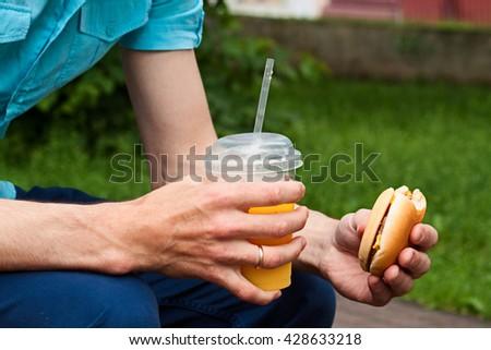 The man eats a hamburger. Dinner time - stock photo
