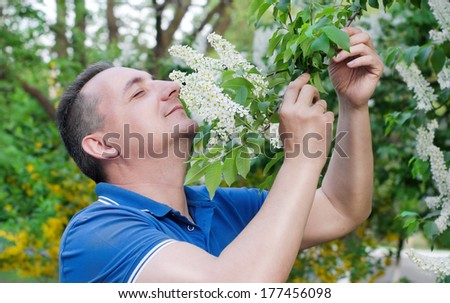 The man enthusiastically sniffing the smell of bird-cherry - stock photo