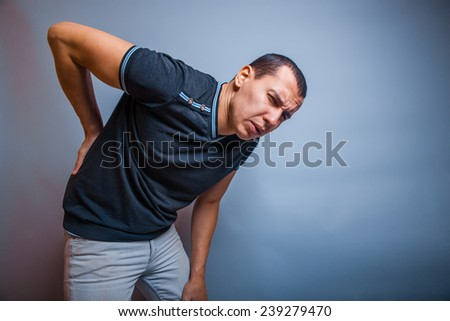 the man European appearance brunet pressed his hand to the back of experiencing pain on a gray background - stock photo