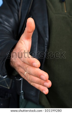 The man extend his hand to shake, close up