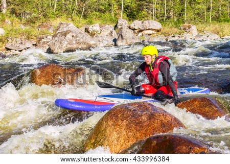 The man fell from SUP surfing on the rapids of the mountain river - stock photo