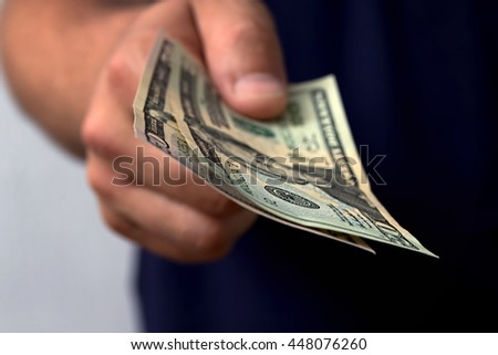 The man gives money. Hand holding out cash. closeup - stock photo