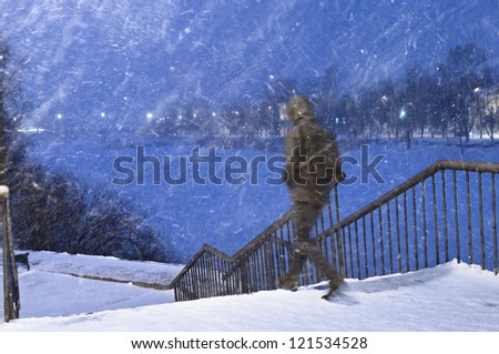 The man going down on steps from the bridge in a heavy snowfall. - stock photo
