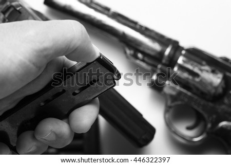 The man hand in holding  action of pistol magazine in the scene appear the gun background represent the weapon and gun concept related idea.