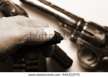 The man hand in holding action of pistol magazine in the scene appear the gun background represent the weapon and gun concept related idea. - stock photo