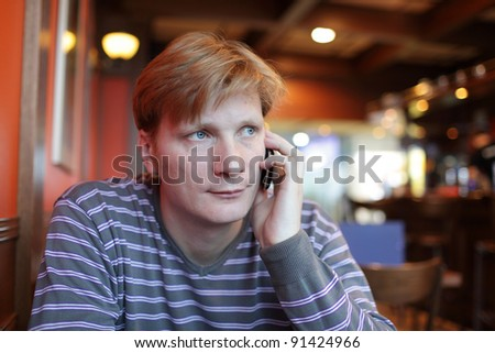 The man has conversation by mobile phone at the restaurant - stock photo