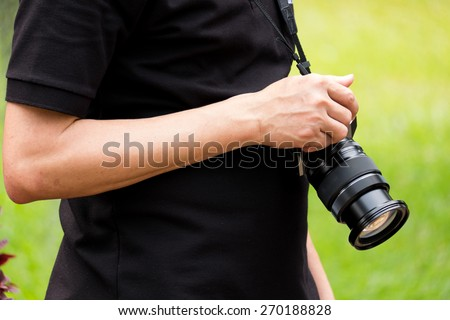 the man hold his camera by right hand - stock photo