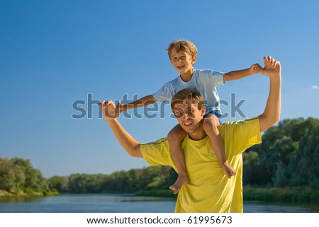 The man holds the boy on shoulders against a landscape