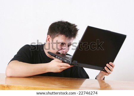 The man in a black vest aggressively bites the laptop
