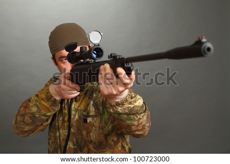 the man in a camouflage aims from a rifle with a riflescope. double 2