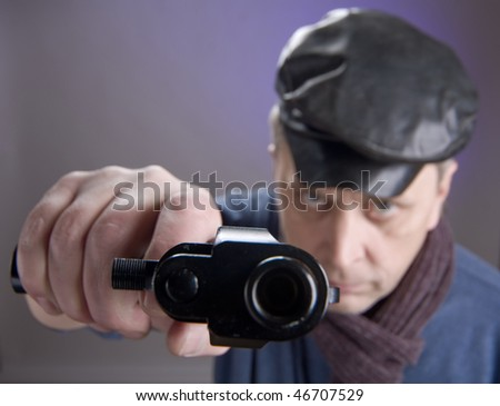 The man in a cap with pistol. Sharpness on hand
