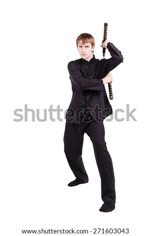 The man in a kimono practicing kung fu. Master holding nunchuck. Fighter isolated on white background. Concept of healthy life and martial arts.