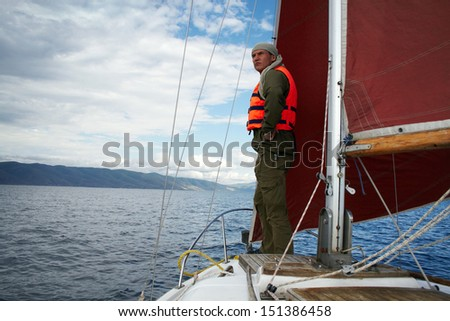 The man in a life jacket costs on a yacht nose, peering afar.