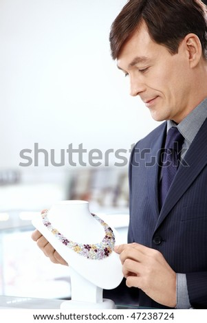 The man in a suit considers a necklace in shop - stock photo