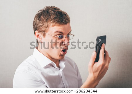 The man in glasses shouts into the phone . On a gray background.
