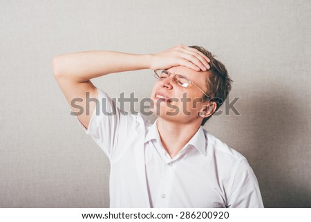 The man in glasses upset sad, hand on his head,. On a gray background. - stock photo