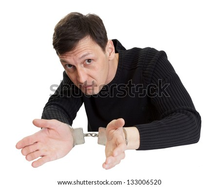 The man in handcuffs interrogatively looks. - stock photo