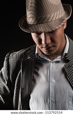 The man in style Chicago gangster on dark background - stock photo