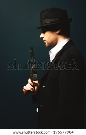 The man in style Chicago gangster with gun on dark background