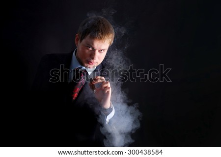 The man in suit smoke a cigar, lots of smoke. A dark background. Looks at us - stock photo