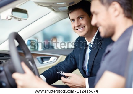 The man in the car with the seller - stock photo