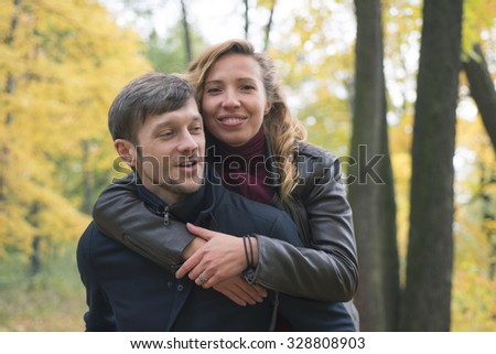 The man in the coat is back, and his young woman hugging and smiling