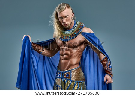 The man in the image of the ancient Egyptian Pharaoh  on blue background - stock photo