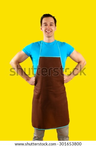 The man in the kitchen wearing an apron holding a rolling pin. isolated