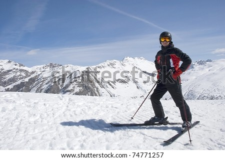 The man in the mountain-skiing form in a helmet and glasses against mountains