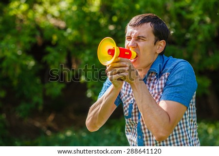 The man in the street holding a plastic speaker shouts on a blue background  summer - stock photo