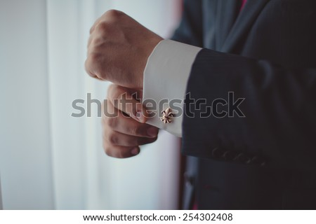 The man in the white shirt in the window dress cufflinks. - stock photo