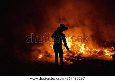 the man is  burning grass in the cold night