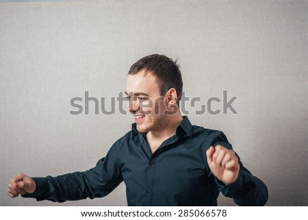 The man is dancing with joy. On a gray background. - stock photo