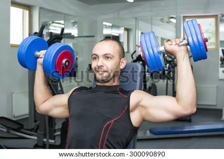 The man is engaged in bodybuilding in the gym